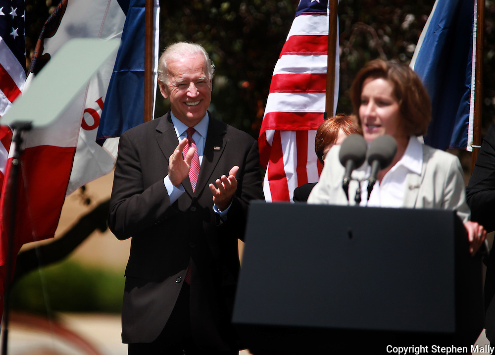 Vice President Joe Biden clapps as he listens to Mariclare Culver, wife of Iowa Governor Chet Culver, at a campaign rally at Green Square Park in Cedar Rapids, Iowa on Tuesday, May 18, 2010.