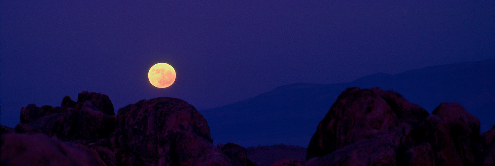 Beautiful, orange, full moon rises over the rugged Alabama Hills in California