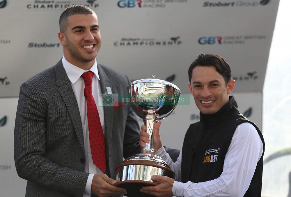 Adam Gemili presents Silvestre de Silva with the Champion Jockey trophy during Qipco British Champions Day at Ascot Racecourse.