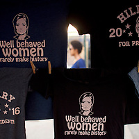 PHILADELPHIA, PA- July 27, 2016.  A woman walks behind Hillary Clinton themed t-shirts, designed by Larry Kleinstein, during a Democratic National Convention themed street festival on Passayunk Avenue on the third day of events in Philadelphia, PA on July 27, 2016.  CREDIT: Mark Makela for The New York Times      NYTDNC