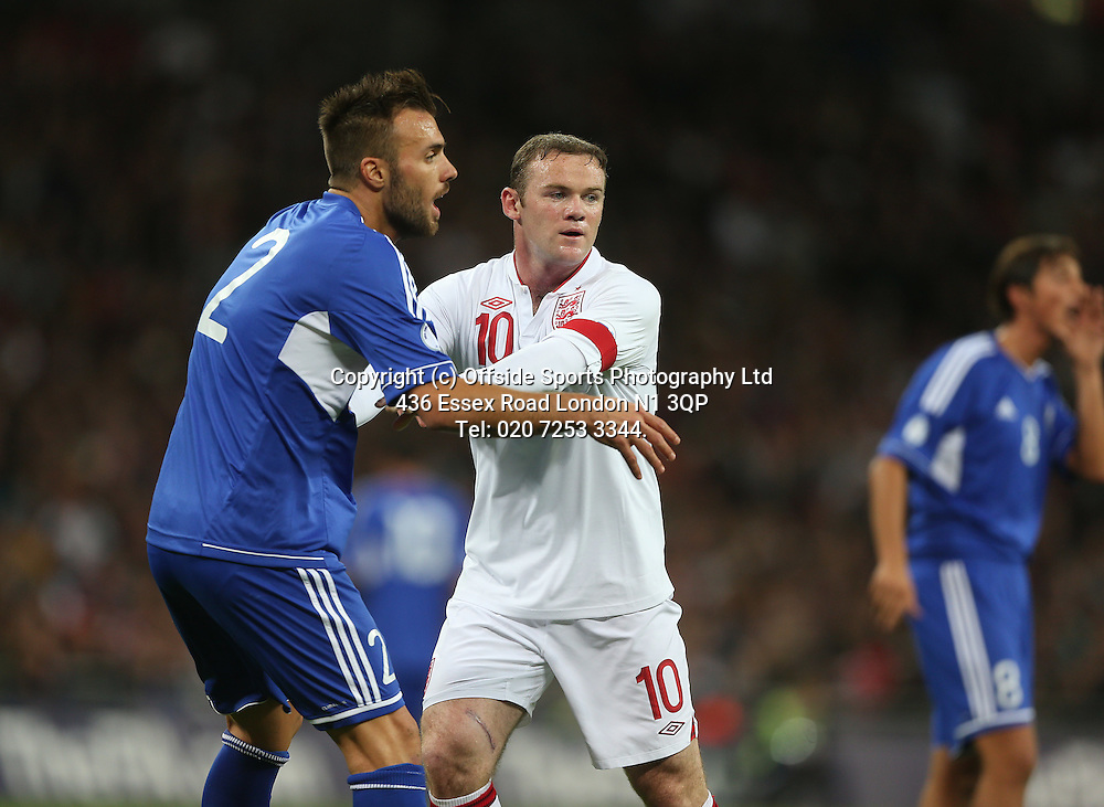 12 October 2012 Football. England v San Marino.<br /> England captain Wayne Rooney is held by Fabio Vitaioli.<br /> Photo: Mark Leech.