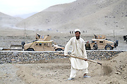 "An Afghan villager tends a field outside a ""Qalat"" used by US mentors living with Afghan National Army soldiers rented from a nearby village in Tagab Valley.  In the background is the graded road being paved to help the valley.....It is part of the counterinsurgency effort to connect with villagers, gather intelligence and provide local security.....Colonel Haynes said fixating solely on the enemy is a mistake.  His men are on the sharp end of the fight taking calculated risks as COIN doctrine prescribes.  The Marines' COIN strategies come from lessons learned by the French and British as well as their own history.  During the Vietnam War the Marines employed a similar COIN idea with some success known as ""Combined Action Programs (CAP's).""  They lived in villages and fought alongside indigenous Vietnamese security forces.  Marine General Victor ""Brute"" Krulak defended the program and waged his own internal policy war with Army General Westmoreland.  Krulak lost his battle with Westmoreland who preferred massive firepower and body counts - a strategy that wreaked havoc on the civilian population.  .."