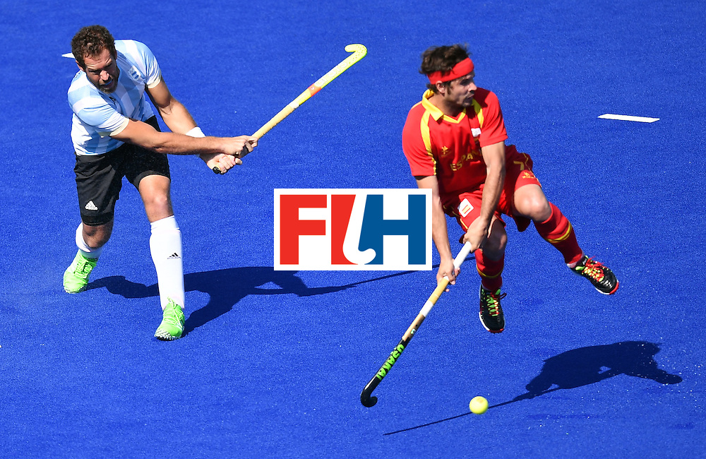 Argentina's Juan Gilardi (L) vies with Spain's Jordi Carrera during the men's quarterfinal field hockey Spain vs Argentina match of the Rio 2016 Olympics Games at the Olympic Hockey Centre in Rio de Janeiro on August 14, 2016. / AFP / MANAN VATSYAYANA        (Photo credit should read MANAN VATSYAYANA/AFP/Getty Images)