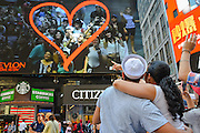 """As a singular example of how both Times Square and human behavior have changed since Eisenstaedt's photograph, a couple from the V-J Day kiss-in marvel at themselves on a display billboard near the exact location of the historic shot. To mark the 70th anniversary of the surrender of the Japanese ending WWII, the Times Square Alliance and """"Spirit of '45,"""" a WWII legacy organization, hosted a kiss-in with members of the public invited to imitate the sailor and nurse in Alfred Eisenstaedt's famous photograph.  (PHOTO: Abin Lohr-Jones/BRAZIL PHOTO PRESS)"""