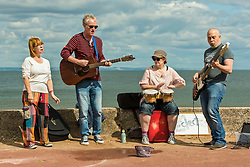 A mile of buskers on Portobello Prom this afternoon in the nonth annual Big Beach Busk. The day starts with the man who first came up with the idea for the busk, ?Paul Lambie and his team of local helpers chalking out the circular 'pittches' all along the Prom. And then the buskers arrive - all ages, all styles of music, from solo performers to big bands. The place is heaving!<br /> <br /> <br /> © Jon Davey/ EEm