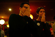 J.P. Avila, left, and Carissa Moncavage watch an announcement on television projecting the election of Barack Obama as president of the United States.