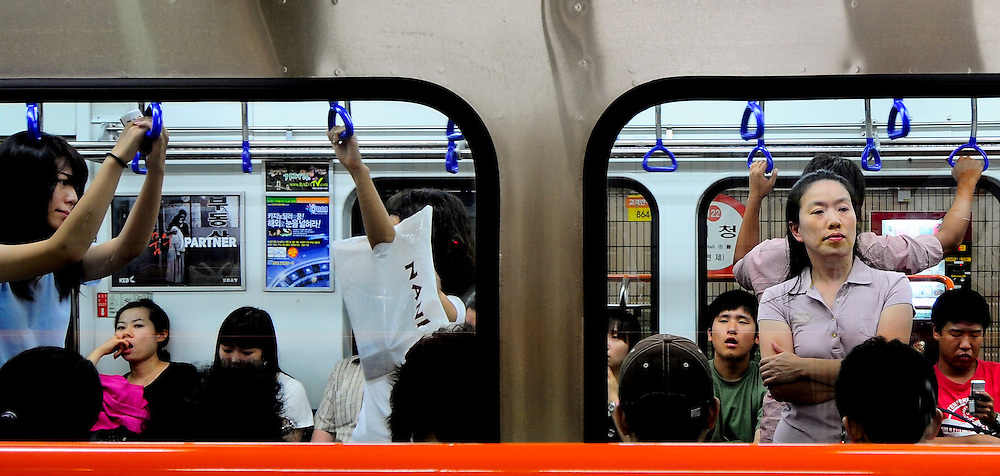 People ride the subway in Busan, South Korea.