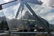 Biking couple and tourist board pyramid in the town of Corvara during the summer walking season in south Tyrol, northern Italy.
