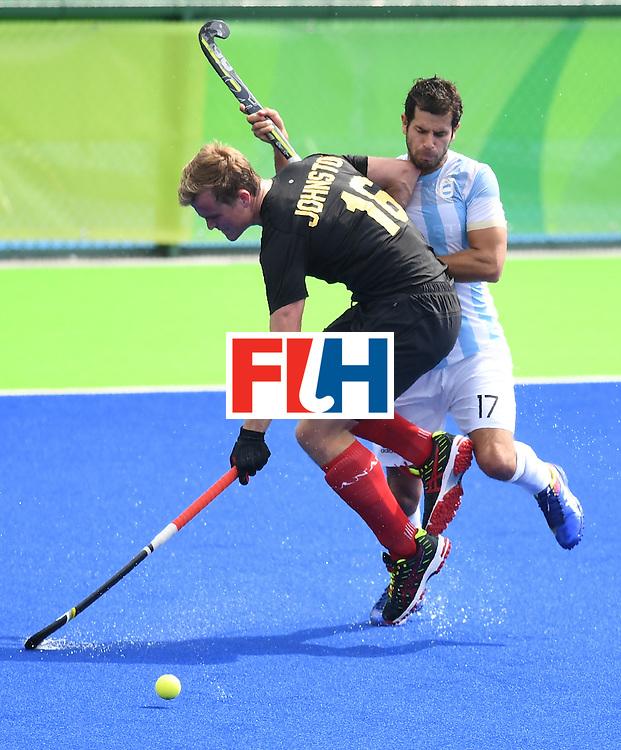 Canada's Gordon Johnston (L) and Argentina's Juan Lopez vie for the ball during the men's field hockey Canada vs Argentina match of the Rio 2016 Olympics Games at the Olympic Hockey Centre in Rio de Janeiro on August, 8 2016. / AFP / MANAN VATSYAYANA        (Photo credit should read MANAN VATSYAYANA/AFP/Getty Images)