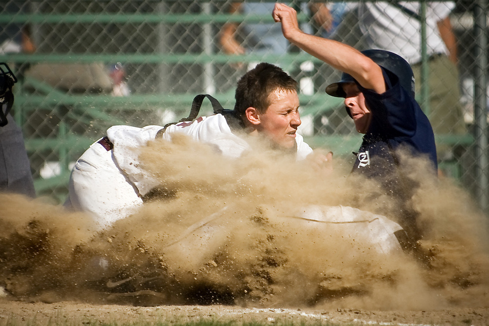 JEROME A. POLLOS/Press..Prairie's Nick Snider attempts to block the plate in a cloud of dust as Coeur d'Alene's Logan Wadsworth safely slides into home.