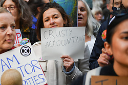 © Licensed to London News Pictures. 17/10/2019. London, UK. Extinction Rebellion protesters came together outside the Department of Work and Pensions to show they are 'not all crusties' but working people wanting to make saving the planet a top job. The flash mob event was entitled 'Suits and Ties Against Ecocide' Photo credit: Guilhem Baker/LNP