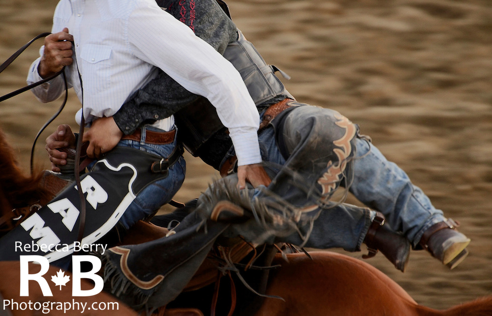 One of Big Stone Rodeo's pickup riders helps a cowboy from his saddle bronc ride at the Mighty Fraser Pro Rodeo during Agrifair in Abbotsford B.C. August 2013.
