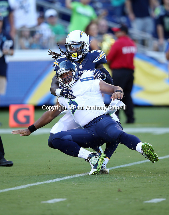 San Diego Chargers defensive back Jahleel Addae (37) sacks Seattle Seahawks quarterback Russell Wilson (3) for a big loss on this first quarter play, due to a penalty added on for intentional grounding, during the 2015 NFL preseason football game against the Seattle Seahawks on Saturday, Aug. 29, 2015 in San Diego. The Seahawks won the game 16-15. (©Paul Anthony Spinelli)