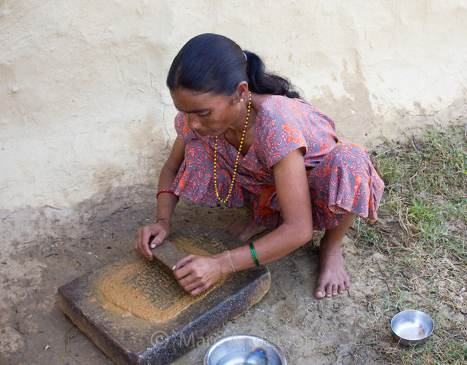 Woman grinding spices and chilli as she is preparing achar (spicy pickle) for a meal in a Tharu village, Nepal