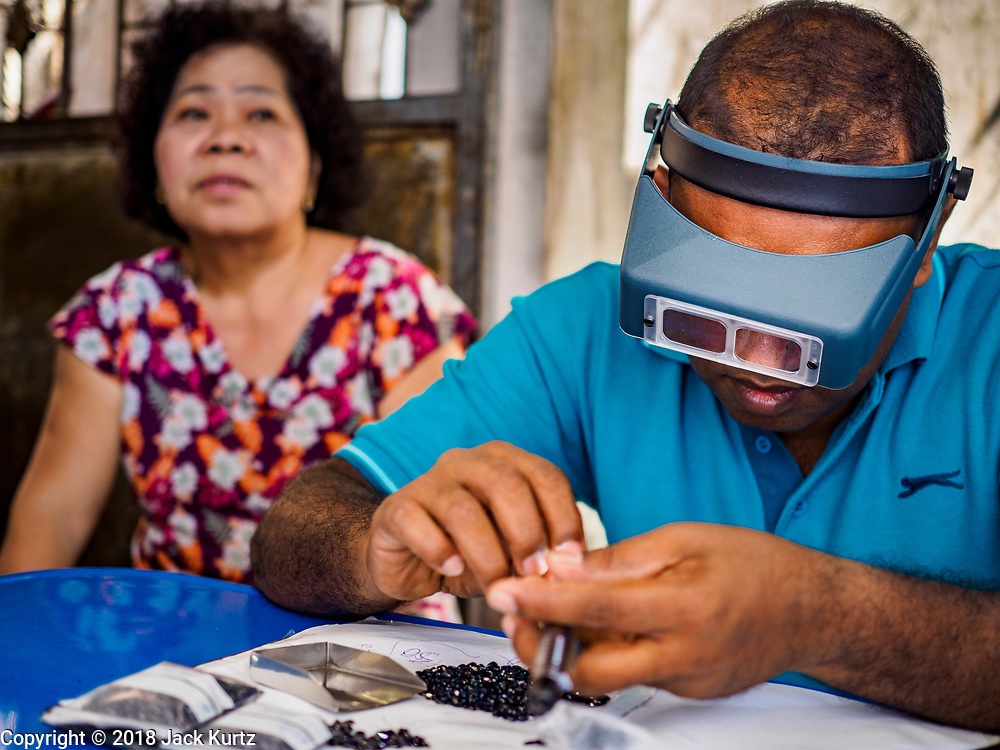 22 DECEMBER 2018 - CHANTABURI, THAILAND: A gem buyer grades gems brought to him in the gem market in Chantaburi. The gem market in Chantaburi, a provincial town in eastern Thailand, is open on weekends. Chantaburi used to be an active gem mining area in Thailand, but the mines are played out now. Now buyers and sellers come from around the world to Chantaburi for the weekend market. Many of the stones come from Myanmar, others come from mines in Afghanistan and Africa.      PHOTO BY JACK KURTZ