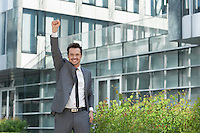 Portrait of cheerful businessman with arm raised standing outside office building