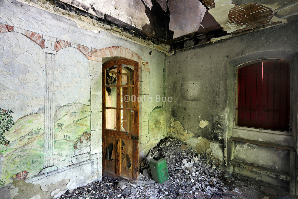 burned out  house with decorative landscape drawing on wall