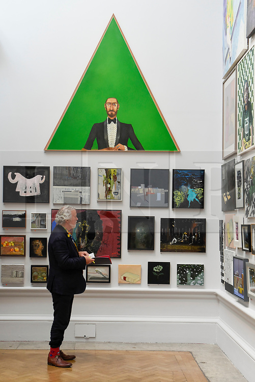 """© Licensed to London News Pictures. 08/06/2017. London, UK. A visitor views artworks on display, overlooked by """"Mr Green Looking At His Wife"""" by Anthony Green RA.  Preview of the Summer Exhibition 2017 at the Royal Academy of Arts in Piccadilly.  Co-ordinated by Royal Academician Eileen Cooper, the 249th Summer Exhibition is the world's largest open submission exhibition with around 1,100 works on display by high profile and up and coming artists.<br />  Photo credit : Stephen Chung/LNP"""