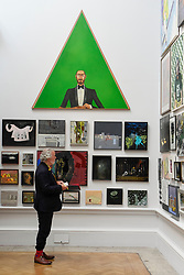 &copy; Licensed to London News Pictures. 08/06/2017. London, UK. A visitor views artworks on display, overlooked by &quot;Mr Green Looking At His Wife&quot; by Anthony Green RA.  Preview of the Summer Exhibition 2017 at the Royal Academy of Arts in Piccadilly.  Co-ordinated by Royal Academician Eileen Cooper, the 249th Summer Exhibition is the world's largest open submission exhibition with around 1,100 works on display by high profile and up and coming artists.<br />  Photo credit : Stephen Chung/LNP