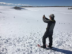 Wildlife photojournalist Noppadol Paothong takes a photo with his iPhone in Wyoming. ©John L. Dengler / DenglerImages.com