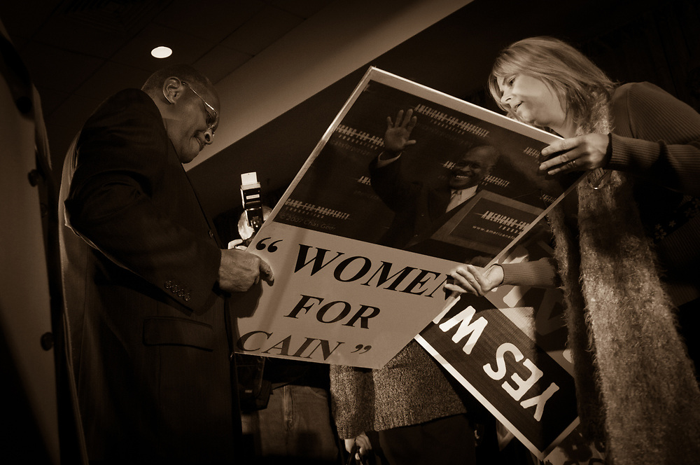 Presidential hopeful Herman Cain signs a sign showing woman's support for him after speaking at a  campaign Rally in the Radisson Hotel in Nashua, NH.