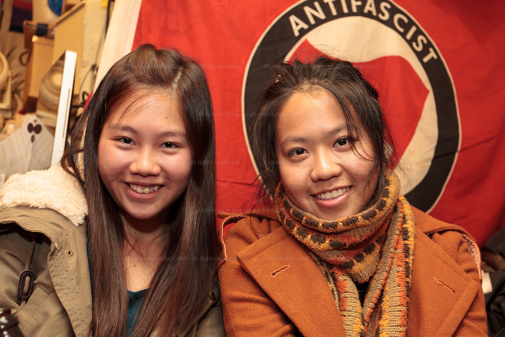 Activist, Alexandra Chan (right) from Hong Kong workers' rights NGO, SACOM sits with a friend after giving a talk at Cafe Lavanderia about workers rights in factories in China that supply Japanese brand Uniqlo. Shinjuku, Tokyo, Japan. Friday, January 16th 2015