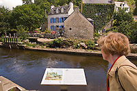 A woman reading the information sign about the moulin Ty Meur depicted in Gauguins les Lavandieres a Pont Aven