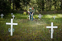 JEROME A. POLLOS/Press..Mallory Fair, 15, with the Pine Tree 4-H Club, rakes pine needles and pine cones off of graves Monday at the Kootenai County Cemetery in Huetter. The Pine Tree 4-H Club overhauled the small cemetery in 1976 and has done annual cleanings every year since.