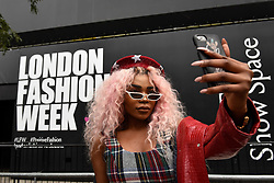 © Licensed to London News Pictures. 14/09/2018. LONDON, UK.  A fashionista takes a selfie outside the home of London Fashion Week in The Strand as London Fashion Week SS19 opens.  Shows featuring many established and up and coming designers are taking place across the capital.  Photo credit: Stephen Chung/LNP