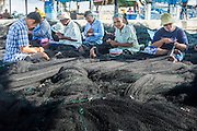 30 APRIL 2013 - MAHACHAI, SAMUT SAKHON, THAILAND: Burmese and Thai workers repair fishing nets in the port of Mahachai, Samut Sakhon province, Thailand. The Thai fishing industry is heavily reliant on Burmese and Cambodian migrants. Burmese migrants crew many of the fishing boats that sail out of Samut Sakhon and staff many of the fish processing plants in Samut Sakhon, about 45 miles south of Bangkok. Migrants pay as much $700 (US) each to be smuggled from the Burmese border to Samut Sakhon for jobs that pay less than $5.00 (US) per day. There have also been reports that some Burmese workers are abused and held in slavery like conditions in the Thai fishing industry.           PHOTO BY JACK KURTZ