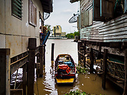 15 AUGUST 2017 - BANGKOK, THAILAND: A small canoe between two homes in a Bangkok riverside community. The community is one of the 14 riverside communities that will be torn down to make way for a riverfront promenade. Construction of the 14 kilometer long promenade will start in late 2017.      PHOTO BY JACK KURTZ