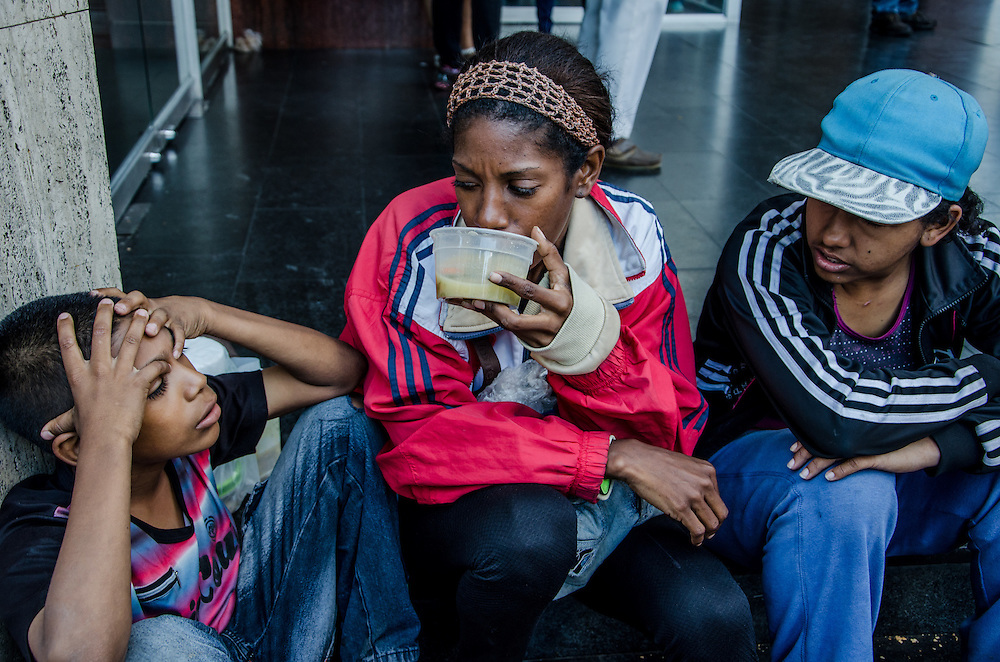 CARACAS, VENEZUELA - FEBRUARY 10, 2017:  Katiuska Tovar, 29, shares a small soup with her son while she works selling cigarettes and candies on the street in downtown Caracas. Ms. Tovar was once worked for the government as an administrative assistant, but had to leave when the government changed payment policies. Ms. Tovar struggles to buy enough food to feed herself and her son with the earnings she makes, so she supplements their diet with food scraps from the garbage. Despite her struggles, she still makes sure her son goes to school, and he earns some of the highest grades in his class. The 2016 ENCOVI (Survey on Living Conditions in Venezuela) found that a skyrocketing percentage of Venezuelan families are struggling to acquire enough food to eat.  Over 90% of the over 6,000 families surveyed reported not having enough income to buy all the food they need. A shocking 73% of survey respondents reported involuntarily weight loss, an average of 8.7kg each for those that said they involuntarily lost weight.  Food and medicine shortages, skyrocketing inflation and the collapse of social programs are causing working class families that once supported the government and Hugo Chávez's socialist revolution to increasingly become disillusioned with the government, and its commitment to the poor. Many once die-hard Chavistas say they feel abandoned, and no longer support the government. PHOTO: Meridith Kohut