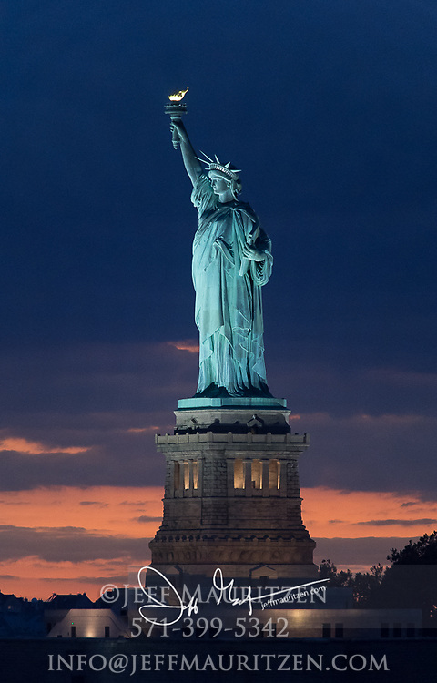 Sunset over the Statue of Liberty as night falls over Liberty Island, NYC.