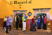 Onlookers step out of a cantina to watch hundreds of people dressed as the skeleton bride La Calavera Catrina parade during the final day of the Day of the Dead festival November 2, 2016 in San Miguel de Allende, Guanajuato, Mexico. The week-long celebration is a time when Mexicans welcome the dead back to earth for a visit and celebrate life.