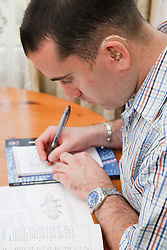 Man with hearing impairment studying book and writing.