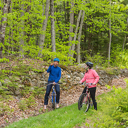A couple mountain biking on a forest trail near Stonehouse Pond in Barrington, New Hampshire.