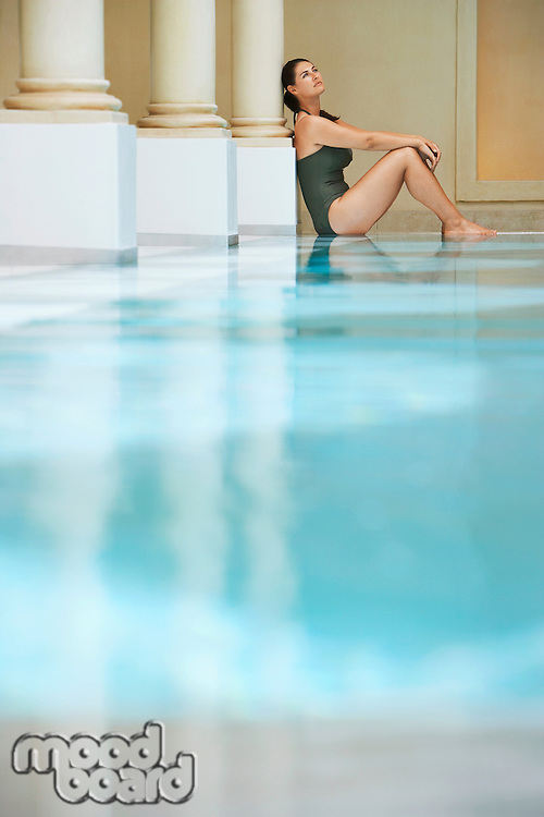 Young woman sitting by swimming pool portrait side view