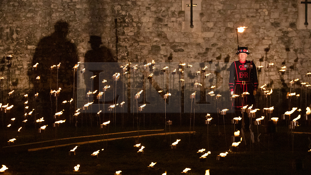 © Licensed to London News Pictures. 04/11/2018. London, UK. A Yeoman Warder watches as thousands of individual flames illuminate the moat of The Tower of London in an installation entitled 'Beyond the Deepening Shadow: The Tower Remembers'. This public act of remembrance for the lives of the fallen, honouring their sacrifice will run for eight nights, leading up to and including the Centenary Armistice Day 2018. The evolving installation will unfold each evening over the course of four hours, with the Tower moat gradually illuminated by individual flames. A specially-commissioned sound installation 'a sonic exploration of the shifting tide of political alliances, friendship, love and loss in war' will be played. At the centre of the sound installation lies a new choral work, with words from war poet Mary Borden's Sonnets to a Soldier. Photo credit: Peter Macdiarmid/LNP