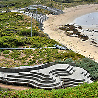 Penguin Parade Viewing Platform on Summerland Peninsula on Phillip Island, Australia<br /> Over 30,000 little penguins live on Summerland Peninsula. Only a faction nest along Summerland Beach, yet they are the star performers at the Penguin Parade Visitor Centre. During the day, this complex is free to explore its exhibits and displays. As the parking lot fills shortly before dusk, you can purchase from among six tour options to watch the world&rsquo;s smallest penguins emerge from the sea and waddle towards their burrows. The eudyptula minor species of penguin, also called the fairy penguin or blue penguin, is only about a foot high. These charming birds have a blue back, white belly and tiny flippers that are useless for flight but ideal for swimming.