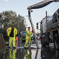 London, UK - 19 September 2014: workmen using suction pumps on Wick Road as torrential rains cause floods and travel disruptions in East London
