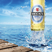 Beck's bottle emerging from the sea next to a pier creating a splash Ray Massey is an established, award winning, UK professional  photographer, shooting creative advertising and editorial images from his stunning studio in a converted church in Camden Town, London NW1. Ray Massey specialises in drinks and liquids, still life and hands, product, gymnastics, special effects (sfx) and location photography. He is particularly known for dynamic high speed action shots of pours, bubbles, splashes and explosions in beers, champagnes, sodas, cocktails and beverages of all descriptions, as well as perfumes, paint, ink, water – even ice! Ray Massey works throughout the world with advertising agencies, designers, design groups, PR companies and directly with clients. He regularly manages the entire creative process, including post-production composition, manipulation and retouching, working with his team of retouchers to produce final images ready for publication.
