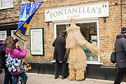 UNITED KINGDOM, Whittlesey: Straw Bear Festival. 'The Bear', traditionally a mischievous straw character, interrupts daily business for a shop owner in Whittlesey during the Straw Bear festival this weekend. The three day festival, which originated in 1882, consists of traditional Molly, Morris, Clog and Sword dancing as well as parading a large straw character known as 'The Bear' through the town. Rick Findler  / Story Picture Agency