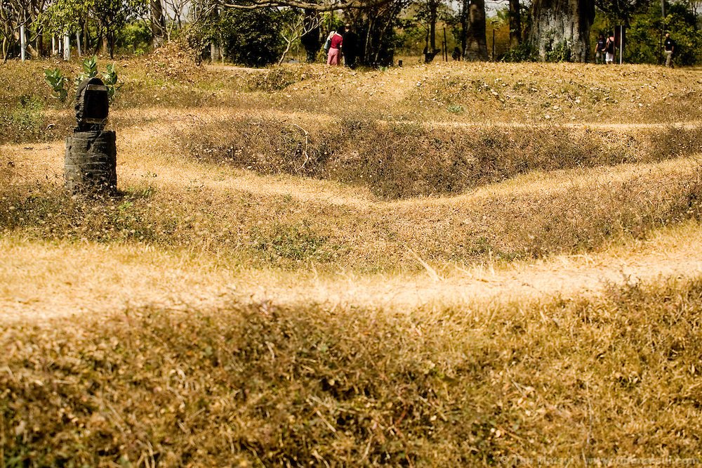 Holes dimple the fields of Choeung Ek where mass graves were excavated at the Khmer Rouge Killing Field near Phnom Penh, Cambodia. 129 mass graves were found of which 86 were excavated. Upwards of 20,000 People were killed by bludgeon, knife, and poison at Choeung Ek, at times at a rate of 300 per day. An estimated 3 million people lost their lives, killed or starved, during the reign of the Khmer Rouge from 1975-1979.