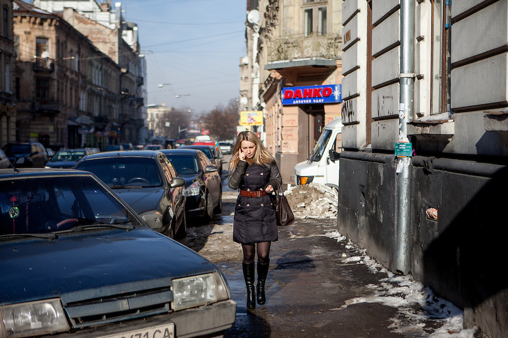 Streetscene in the city center of Lviv. A woman using her mobile phone.
