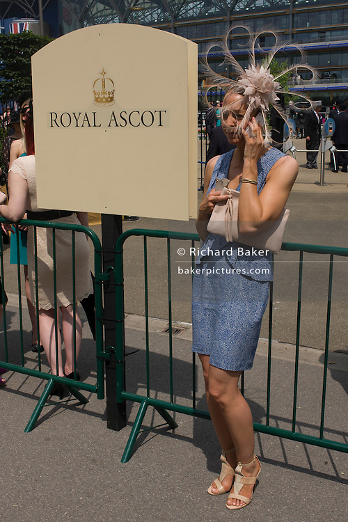 Lady wearing an extraordinary hat makes a call on her smartphone during the annual Royal Ascot horseracing festival in Berkshire, England. Royal Ascot is one of Europe's most famous race meetings, and dates back to 1711. Queen Elizabeth and various members of the British Royal Family attend. Held every June, it's one of the main dates on the English sporting calendar and summer social season. Over 300,000 people make the annual visit to Berkshire during Royal Ascot week, making this Europe's best-attended race meeting with over £3m prize money to be won.