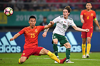 Harry Wilson, right, of Wales national football team kicks the ball to make a pass against He Guan of Chinese national men's football team in the semi-final match during the 2018 Gree China Cup International Football Championship in Nanning city, south China's Guangxi Zhuang Autonomous Region, 22 March 2018.