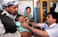 KABUL 06 August 2005..Maiwand Hospital..Janat is holding Shabana while Dr Aminullah Hamkar examines her lump. He is the Doctor who will perform Shabana Plastic Surgery on the 16th of August.....Shabana. a nine months old Afghan girl, has been diagnosed with a 'neurofibroma'. This is a tumor or growth located along a nerve or nervous tissue. It is an inherited disorder. If left unchecked, a neurofibroma can cause severe nerve damage leading to loss of function to the area stimulated by that nerve.....The Rehabilitative Surgery Unit (RSU) at Maiwand Hospital is fully supported by  the French NGO Medical Refresher Courses for Afghans (MRCA), also by the French Minister of Foreign Affairs, and by the Embassy of Japan under the Grant Assistance for Grassroots Project (GAGP). The Italian NGO Operation Smile Italia Onlus  provides training to the Doctors. ....Maiwand Hospital dates back to the rein of Nadir Shah in the 1930s.