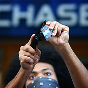 A protester cuts up a bank card during the Occupy Seattle protest in front of Chase Bank on 4th Avenue on Saturday, October 15, 2011 in Seattle. About 5,000 people joined protesters that have been camped at Westlake Park for two weeks. The demonstration is an offshoot of the Occupy Wall Street protest in New York. Saturday was dubbed as a global day of action by the movement. (Joshua Trujillo, seattlepi.com)