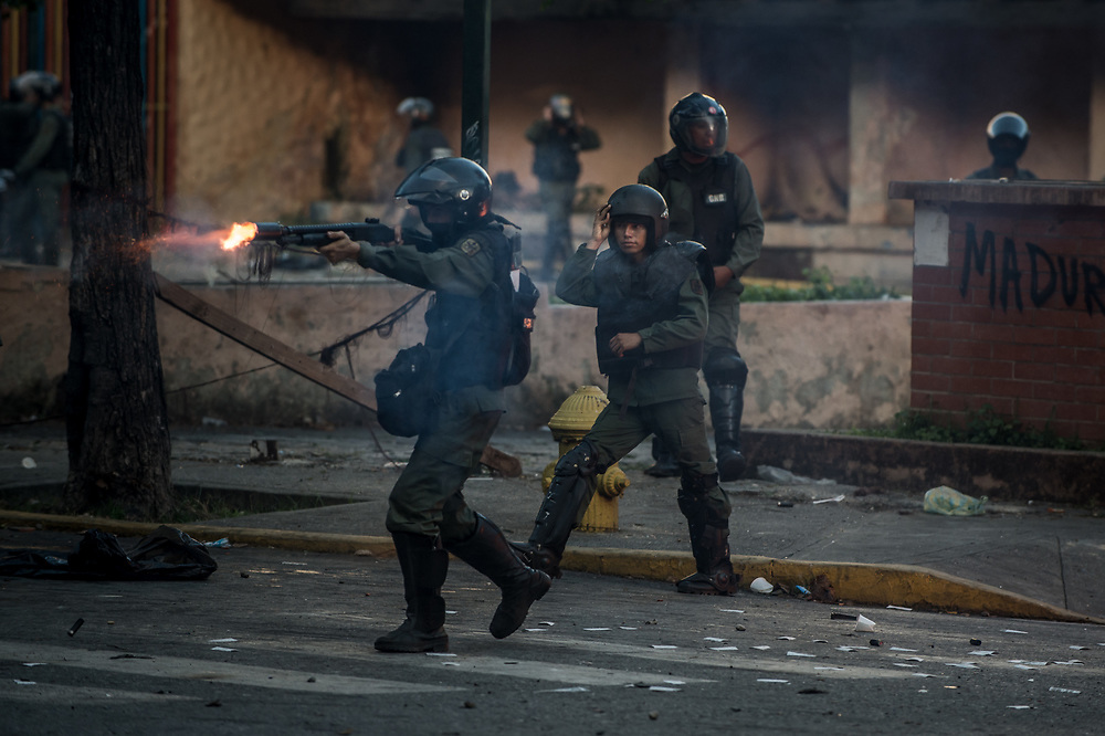 CARACAS, VENEZUELA - JULY 26, 2017: Soliders fire tear gas at members of La Resistencia during an anti-government protest. Protesters took to the streets to demand that the National Constituent Assembly election scheduled for Sunday, July 30th be cancelled. The political opposition called for a 48 hour national strike on July 26th and 27th, and for their supporters to close businesses, not go to work, and instead create barricades to block off their streets.  Opposition controlled areas of the country were completely shut down.  The strike was called as part of the opposition's civil resistance movement - that began on April 1st, to protest against the Socialist government's attempt to elect a new assembly that will have the power to re-write the constitution, and their opposition to the Socialist's continued threats to Venezuelan Democracy.  PHOTO: Meridith Kohut for The New York Times