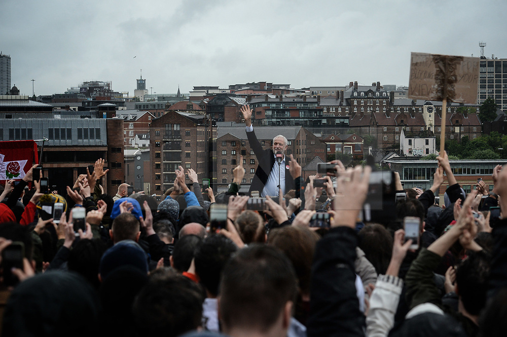 © Licensed to London News Pictures. 05/06/2017. Newcastle Upon Tyne, UK.  Jeremy Corbyn MP, Leader of the Labour Party, waves to a crowd of hundreds of his supporters who waited in the rain to hear him speak outside the Sage in Gateshead. Mr Corbyn spent one of the final days of the campaign trail in the Labour heartlands of North-East England before voters go to the polls in the UK General Election on June 8th 2017. Photo credit: MARY TURNER/LNP
